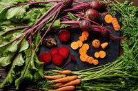 Top view at vegetable background of beets and carrots on kitchen table close up view