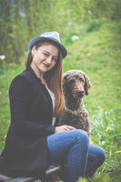 Spring: elegant young woman with hat and dog 20 - 30 years, enjoys the sunshine in the garden.