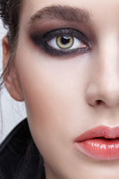 Closeup macro portrait of female face.  Girl with perfect skin, green pistachio colour eyes and violet - black smoky eyes make-up.