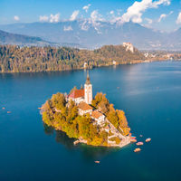 Aerial view of Bled island on lake Bled, and Bled castle and mountains in background, Slovenia.