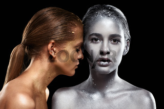 Beauty portrait of young gorgeous women. Golden and silver girls on black background