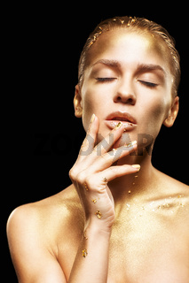 Female with  closed eyes and hands near face. Golden girl on black background
