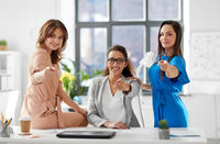 group of businesswomen pointing to you at office