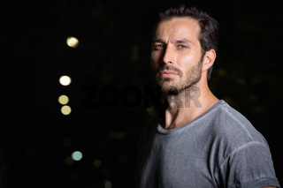 Face of handsome bearded man outdoors at night