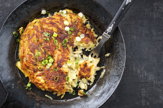 Traditional Swiss rosti as side dish with leek as top view in a frying pan with copy space right