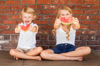Cute Young Cuacasian Boy and Girl Eating Watermelon Against Brick Wall