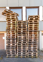 Stack of used wooden pallets in a backyard