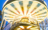 moving and unfocused effect of a merry-go-round with colorful lights at dusk at an amusement park