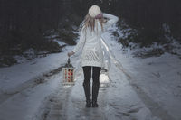 Woman walking along an icy road in winter with lantern