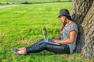 Woman works on laptop at tree in nature