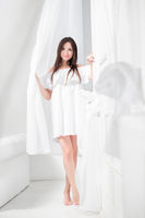 Young alluring brunette dressed in a white dress.