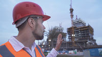 Man in a helmet, architect, engineer, manager tells about the progress of construction in evening
