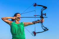 Young colombian woman aims arrow of compound bow