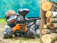 A paintball player who is ready to shoot from hiding. Lying on the ground and shooting. Immediately