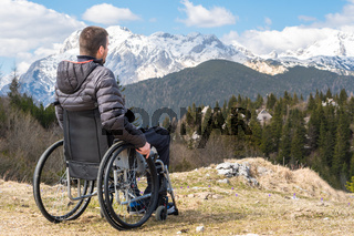 Young disabled man in wheelchair outside in nature observing mountains and nature