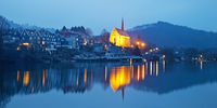 Beyenburg storage lake and illuminated St Mary Magdalena church in the evening, Wuppertal