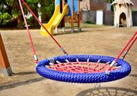 Close-up of colorful blue-red nest swing seat in the playground.