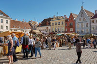 Tourists crowd enjoying shopping at the medieval Town Square in the walled city of Tallinn Estonia.