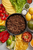 Ingredients for Chili con carne in frying iron pan on white wooden table