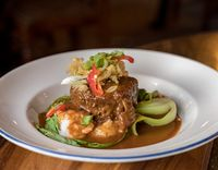 Beef Rendang curry in white bowl on pub table