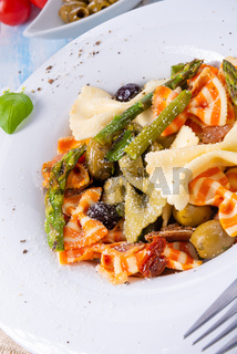 colorful farfalle with green asparagus olives and parma ham