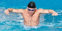Panorama of Muscular swimmer young man in black cap in swimming pool, performing butterfly stroke.