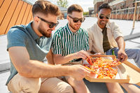 male friends eating pizza with beer on rooftop