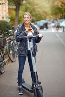 Young woman with electric kick scooter