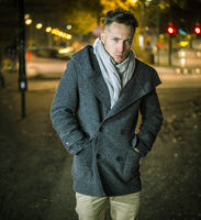 Handsome trendy young man, standing on a sidewalk at night