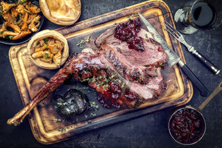 Marinated sliced barbecue aged leg of venison with chanterelles and Yorkshire pudding as top view on a rustic board