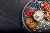 Flat lay view at vintage tray with ripe organic bilberry raspberry strawberry oat cookies and almonds set on slate closeup