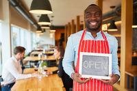 Kellner hält eine Kreidetafel mit Schrift Open