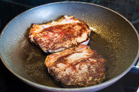 two roasted piece of meat in frying pan on range