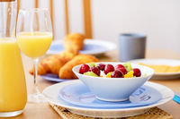 Close up fresh healthy nutritious breakfast jug glass with orange natural juice croissants on background, bowl plate with porridge or cereals garnished cherry, kiwi, orange slices on wicker place mat