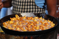 Man frying spicy snack or entree dish similar to a fritter, bhajji on street