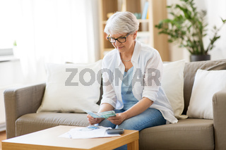 senior woman counting money at home