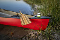 red canoe with lantern on a lake shore