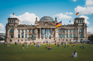 Many people on meadow in front of the Reichstag building (German Bundestag), a famous  landmark on a sunny, summer day
