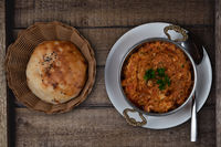 Turkish meze, acili ezme or spicy paste on rustic wooden background