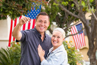 Happy Couple With New House Keys In Front of Houses with American Flags