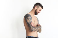Fashionable shirtless man with tattoo posing in jeans