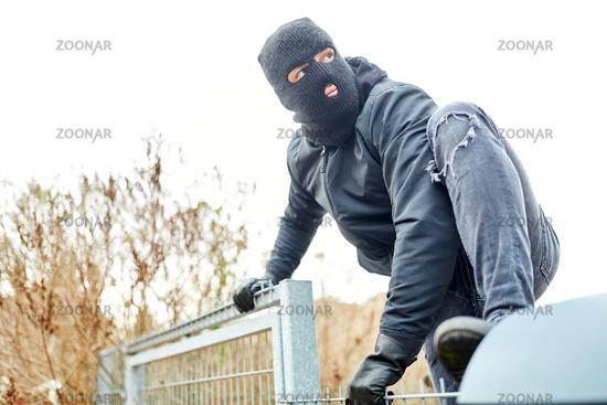 Vermummter Einbrecher klettert über Zaun