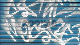 Blue garage gate with graffiti