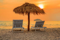 Beach lounge chairs under parasols on tropical beach at sunset