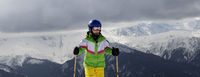Young skier with ski poles in sun mountains and gray sky before storm
