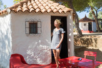 Woman enjoying relaxing summer vacations in authentic vintage bungalow of camping village under mediterranean pine trees, Palau, Sardinia, Italy.