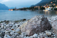 Heavy rock on the beach, blurry background with lake and village, evening