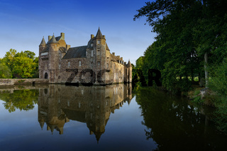 the historic Chateau Trecesson castle reflected in the pond in cool dark blue evening light