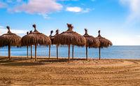 Straw umbrellas on empty seaside beach