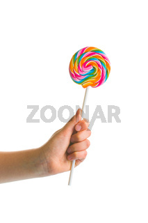 Swirl colorful lollipop in child hand.